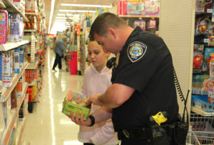 Officer Nolan Smith shops with Kaylee Place at Kmart during Shop With A Cop Saturday morning. Jillian Danielson/RiverScene