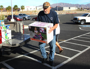 Jay Meyers carries a toy into the Toys For Tots shop Tuesday afternoon. Jillian Danielson/RiverScene