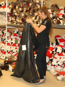 Samantha Hoffman of the LHHS Key Club, places a stuffed animal in a bag for a family Tuesday afternoon. Jillian Danielson/RiverScene