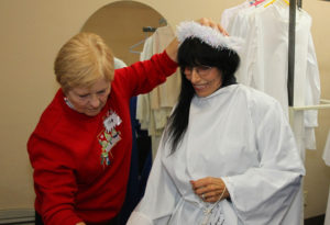 Jan Markham assists Adele Diaz with her angel costume Thursday night during dress rehearsal. Jillian Danielson/RiverScene