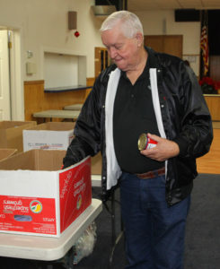 Larry Westerfield places cans of food in boxes for families Friday morning. Jillian Danielson/RiverScene