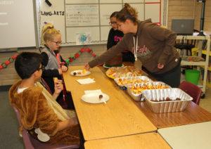 Jessalyn Garcia and Lawae Weissman serve Kadenz Kathers and Andrew Tadia samples of food during Taste of Sixth Grade Thursday morning. Jillian Danielson/RiverScene