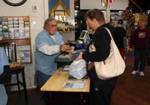 Jim McCullough assists Sylvia Woodall at the register Wednesday. Jillian Danielson/RiverScene