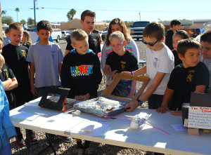 Ryder and his classmates watch a sixth grader do a demonstration about solar energy.