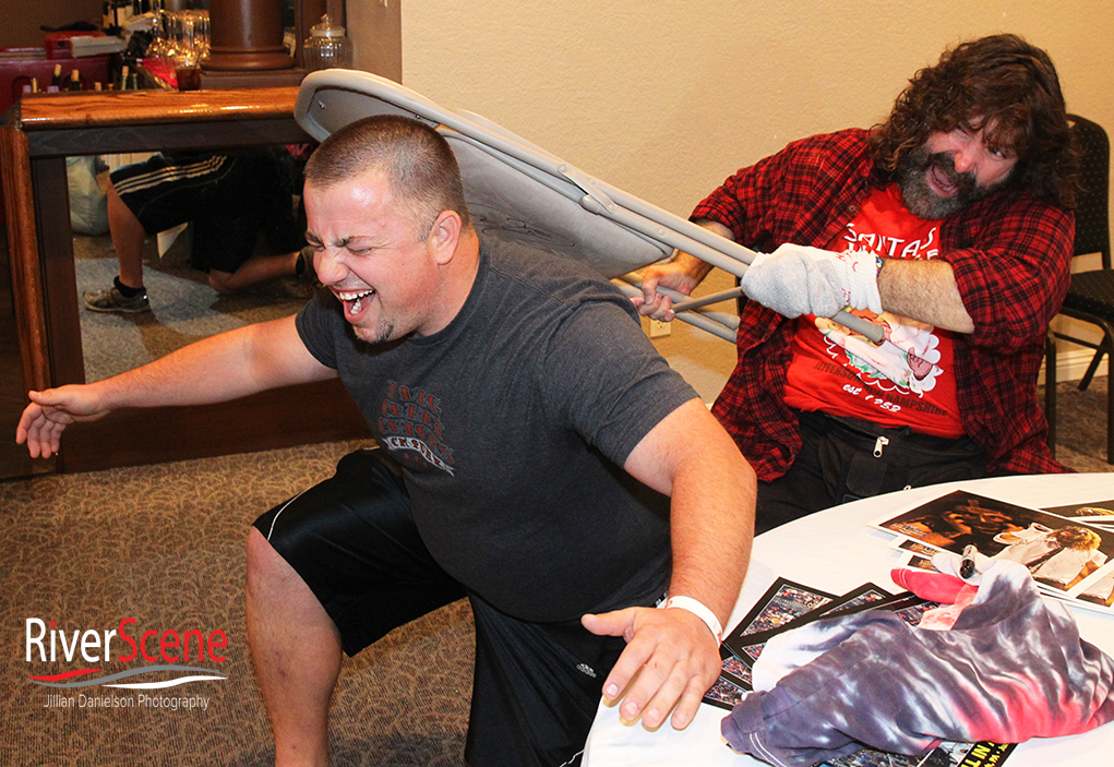 John Jones pretends to have Mick Foley hit him with a chair at the London Bridge Resort.
