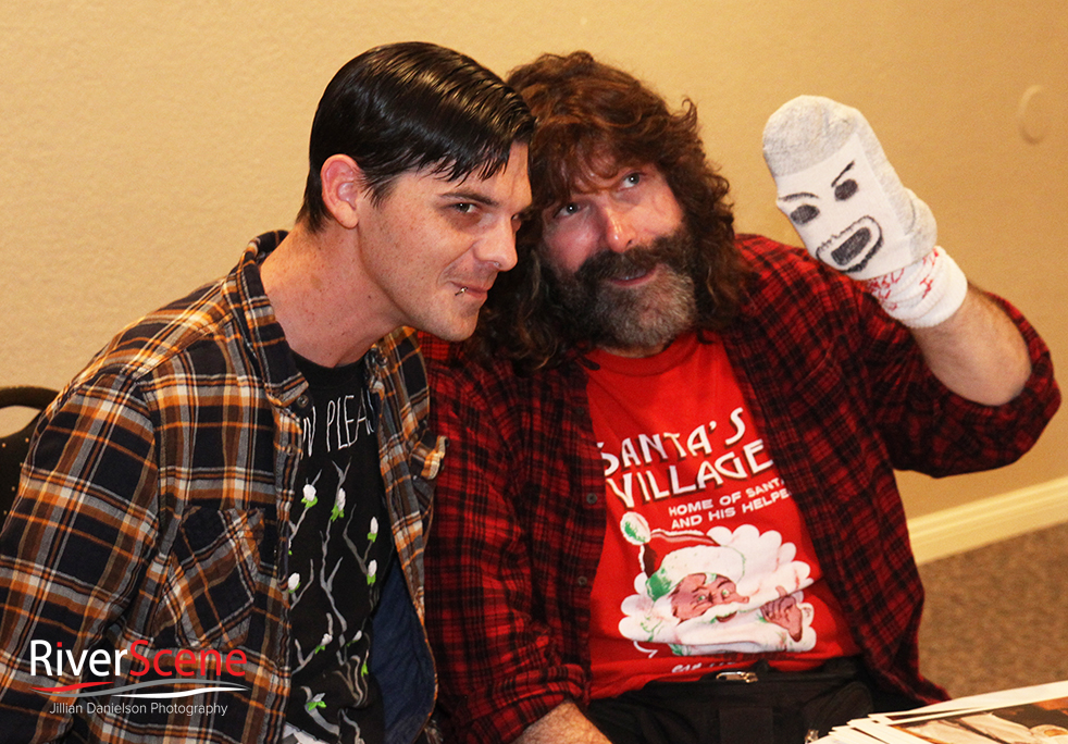 A fan takes a photo with Mick Foley during a Pennington's Pub comedy night .