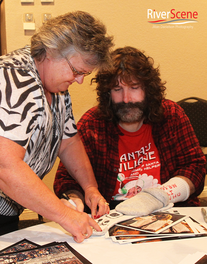 Mary January gets a sock autographed Saturday evening by Mick Foley.