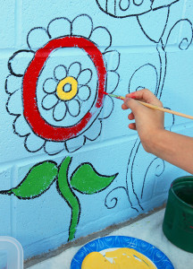 Emilee Gregg paints a flower on the wall of HAVEN Saturday morning. Jillian Danielson/RiverScene