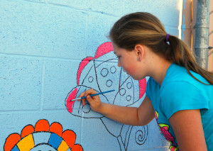 Madison Walkinshaw paints a wall on the HAVEN patio Saturday morning. Jillian Danielson/RiverScene