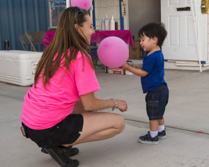 """Cinco Schott, Age 2 receives a balloon from Heather Courneya. Heather is one of many volunteers and the organizer of the 6th annual """"Denise's Day"""" Fundraiser. Denise's Day raises monies for Lake Havasu families impacted by Cancer. The event was held Saturday night at the rodeo grounds.  Mark Russell/RiverScene"""