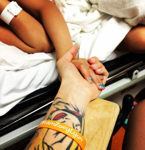 Zoey hold her mom's hand during a chemo treatment.