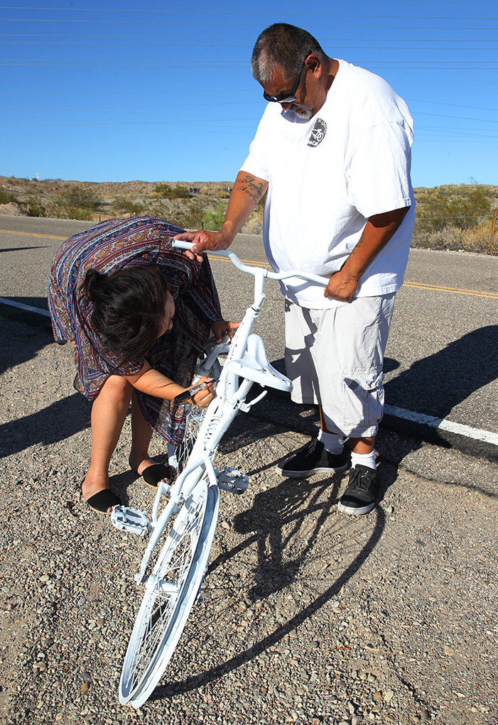 Angelique Martinez signs one of the bikes in memory of Deborah Robinson and Larry Smith. Jillian Danielson/RiverScene
