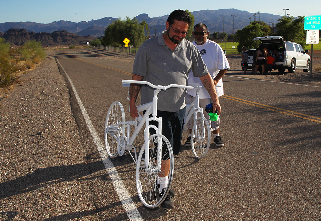 """Junior"" Santiago and Anthony Martinez walk to the side of Highway 95 to place the bikes Wednesday afternoon. Jillian Danielson/RiverScene"