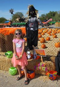 Kaytlyne Edwards poses with RiverScene's scarecrow Saturday morning. Jillian Danielson/RiverScene