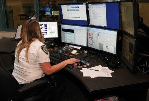 A dispatcher looks over her computers at the police department. Jillian Danielson/RiverScene