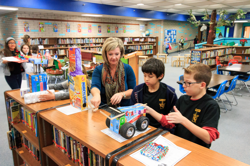 Mrs Christie Olsen, Academic Coaching, helps students place their Elf Engineering toys and games in the Nautilus School Library.