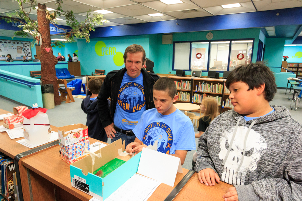 Dr. Ryan Jeannette, ASU Professor and volunteer judge, looks on as s Nautilus STEM Club student plays with one of the Elf Engineering designed games.