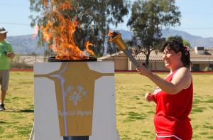Angel Swantik lights the torch Saturday morning. Jillian Danielson/RiverScene