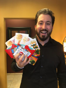 Dustin Runyon holds gift cards that he is donating to the event.