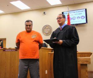 Graduate Carlos Rodriguez receives certificate from Judge Kalauli. Rick Powell/RiverScene