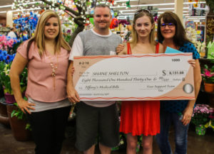 Ashley Lett, Shane, Tiffany and Erica Sheldon pose with a check that was donated for Tiffany's medical expenses. Rick Powell/RiverScene