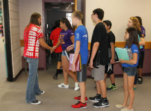 Thunderbolt students shake hands with their teacher as they enter the classroom Thursday morning.
