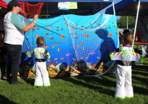 Twins Wyatt and Logan Lauer, dressed as Buzz Lightyear, play a fishing game Saturday at the Fall Fun Fair. Jillian Danielson/RiverScene