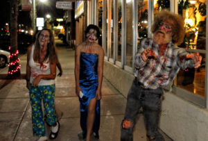 Eve Bartheld, and Ana and Mike LoCurto walk down McCulloch Blvd. Saturday evening dressed as zombies. Jillian Danielson/RiverScene