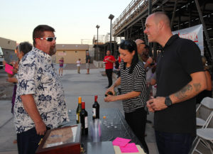 Levi French and Kimberly Carter volunteer for the Lake Havasu Cigars booth Tuesday evening. Jillian Danielson/RiverScene
