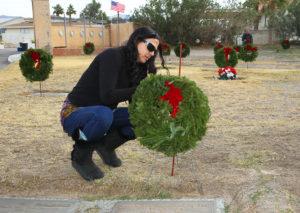 Rebecca White places a wreath on a Veteran's grave site Wednesday morning at Havasu Memorial Gardens. Jillian Danielson/RiverScene