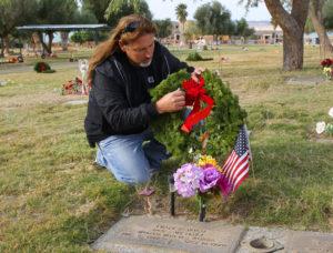 Dallas Finch places a wreath on a Veteran's grave site Wednesday morning at Havasu Memorial Gardens. Jillian Danielson/RiverScene