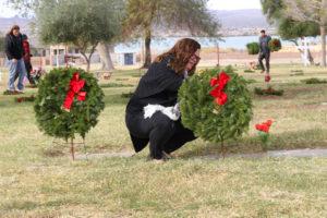 Kristina Gallo places a wreath on a Veteran's grave site Wednesday morning at Havasu Memorial Gardens. Jillian Danielson/RiverScene