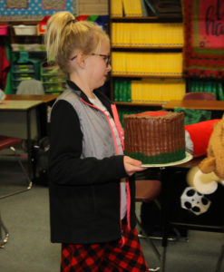 Kadenz Kathers carries a cake she made for the Taste of Sixth Grade. Jillian Danielson/RiverScene