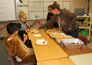 Jessalyn Garcia and Lawae Weissman serve Kadenz Kathers and Andrew Tadia samples of food during Taste of Sixth Grade Thursday morning. Jillian Danielson/RiverScene