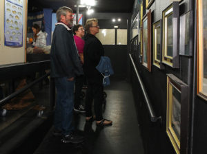 Gary and Eynon Petter, Onterio, Canada, and Sylvia Woodall, Coeur d' Alene Idaho, look at photos on a wall at the Visitors Center Wednesday afternoon. Jillian Danielson/RiverScene